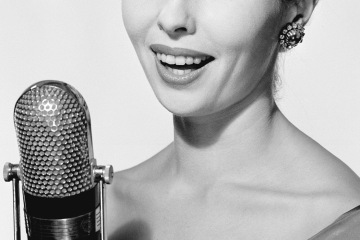 Studio portrait of young woman singing into microphone